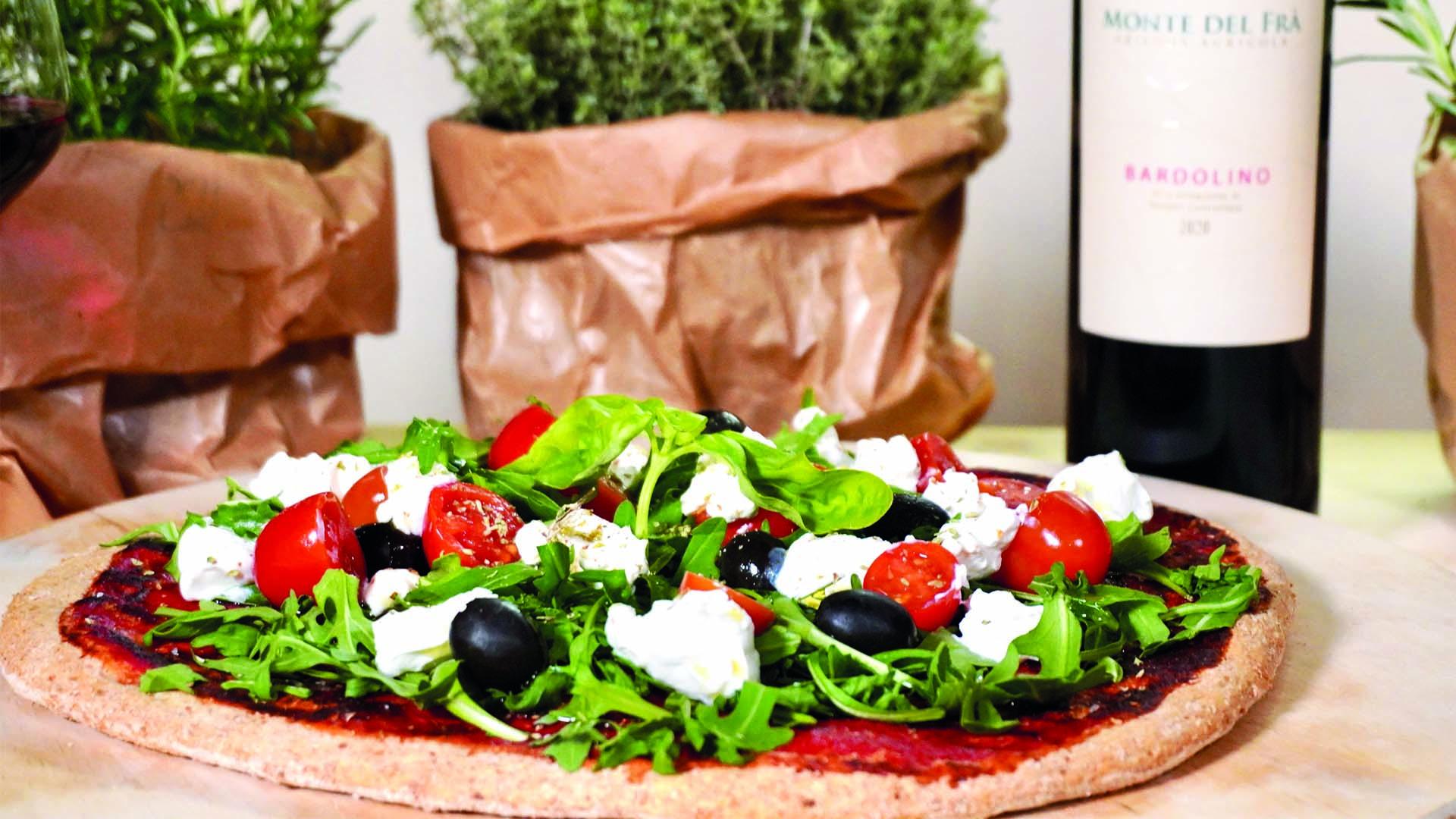 Pizza fatta in casa con ottimo vino rosso della zona del Garda